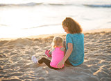 Young mother and daughter in workout gear sitting on beach