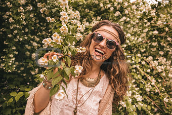 smiling bohemian young woman holding branch of flowers