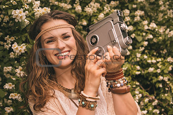 portrait of bohemian young woman among flowers with retro camera