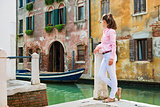 Woman tourist taking a break by one of Venice's canals