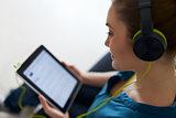 Woman With Green Headphones Listens Podcast Music On Tablet PC