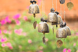 Detail view of vintage bronze bells with colorful bokeh