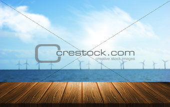 3D background of a wooden table looking out to a wind farm in th