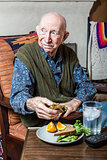 Elderly Man Holding Sandwich
