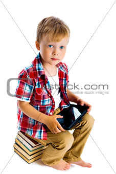 boy with a Tablet PC sitting on the books