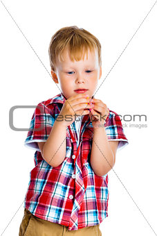 little boy stands and examines small toy