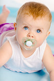 Beautiful baby with a pacifier. Close-up. Studio photo