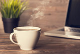 Hot coffee on wooden office desk