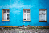 Three windows on a blue wall