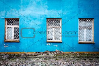 Three windows on a blue wall