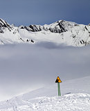 Warning sing on ski slope and mountains in fog