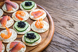 Canape with seafood on the wooden board