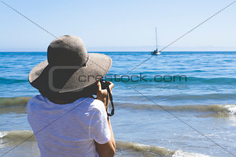 Tourist Taking a Picture of a Boat on the Ocean