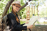 woman holding a map in the park