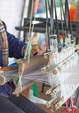 Woman weaving white pattern on loom