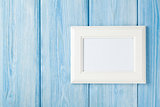 Photo frame on blue wooden wall