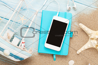 Smartphone and notepad on sea sand with starfish and toy boat