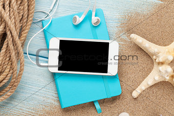 Smartphone and notepad on sea sand with starfish