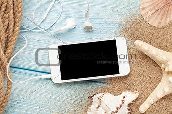 Smartphone on wood and sea sand with starfish and shells