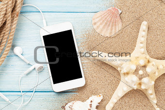Smartphone on wood and sea sand with starfish and shells