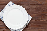 Empty plate over wooden table background