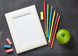 Photo frame and school supplies on blackboard background