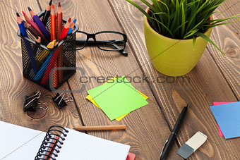 Office table with flower, blank notepad and supplies