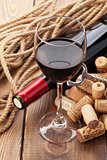 Glass of red wine, bottle and corks