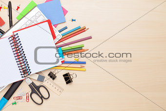 Blank notepad over school and office supplies