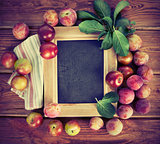 Board for text with fresh plums and green leaves