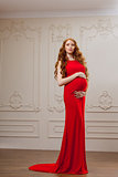 Pregnant fashion model in red dress