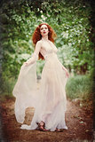 Gorgeous redhead woman wearing white dress in a forest. Grunge texture effect