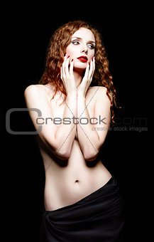 Studio portrait of beautiful red-haired woman on black background