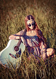 Lovely young hippie girl with guitar sitting on grass