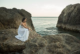 Beautiful woman sitting on a stone