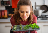 Woman with eyes closed smelling fresh herbs