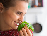 Closeup of smiling woman holding up and smelling fresh basil