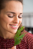 Closeup of smiling woman holding up and smelling fresh dill