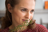 Closeup of woman smelling fresh thyme