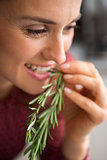 Closeup of smiling woman tasting fresh rosemary