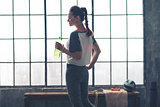 Profile view of fit woman holding water bottle in loft gym