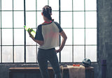 Rear view of woman looking out of loft gym holding water bottle