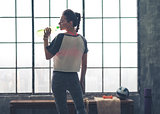 Fit woman in workout gear in profile drinking from water bottle