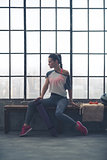 Fit woman in workout gear sitting on bench in loft gym