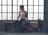 Woman in workout gear posing in profile on loft gym bench
