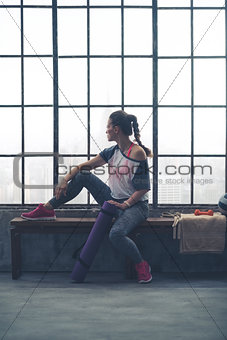 Fit woman sitting on loft gym bench looking out window