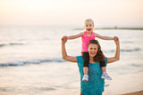 Joyful mother holding daughter on shoulders on beach at sunset