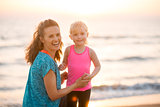 Portrait of young mother and daughter in workout gear on beach