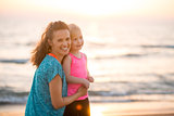 Portrait of happy young mother and daughter on beach at sunset