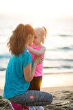 Fit young mother and daughter on beach giving Eskimo kisses